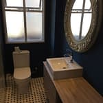 Bathroom renovation with new frameless shower, toilet, vanity and basin.