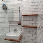 Bathroom renovation with frameless shower panel, subway tiles, kiaat shelves and new basin